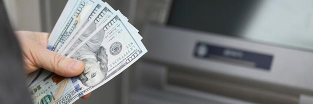 Een man in een jas heeft dollars op straat in de buurt van een pinautomaat met een beveiligd wachtwoord voor contant geld Premium Foto