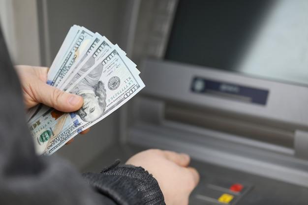 Een man in een jas heeft dollars op straat in de buurt van een pinautomaat met een beveiligd wachtwoord voor contant geld