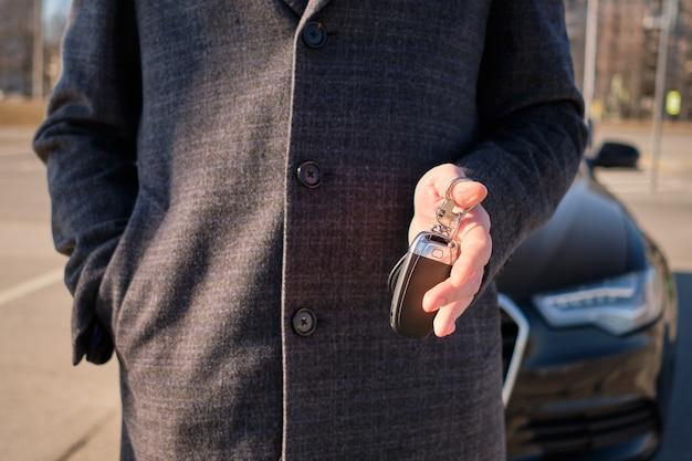 Een man in een jas heeft sleutels op de achtergrond van een moderne auto. verhuur concept.