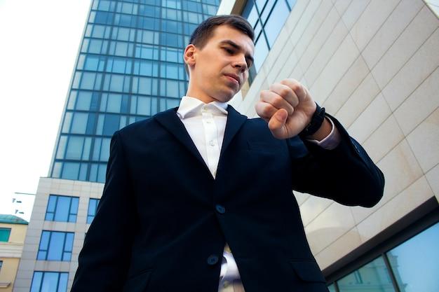 Een man in een jas kijkt op zijn horloge
