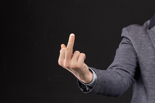 Een man in een jas laat je zien neuken met zijn hand op een zwarte achtergrond.