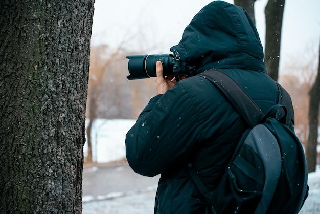 Een man in een jas met een capuchon en een koffer op zijn rug, een camera vasthouden en foto's maken