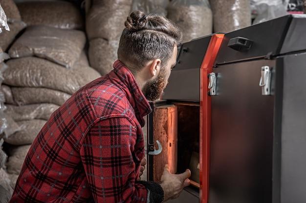 Een man in een kamer met een vastebrandstofketel, bezig met biobrandstof, zuinige verwarming.