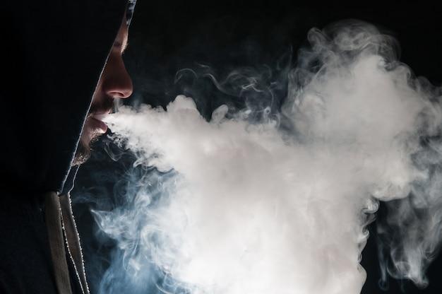 Een man in een kap rookt een elektronische sigaret.