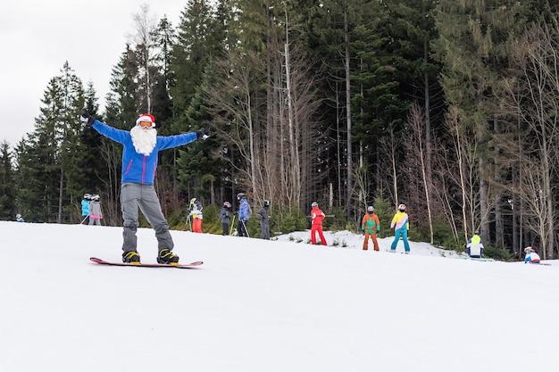 Een man in een kerstmuts met een snowboard in een skiresort.