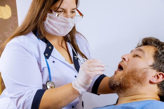 Een man in een klinische setting die tijdens het bepalen van de behandeling het coronavirus covid-19 opliep, werd door een arts onderzocht.