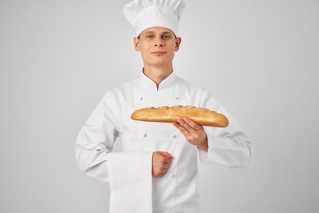 Een man in een koksuniform die een broodbakker vasthoudt die voedsel bereidt
