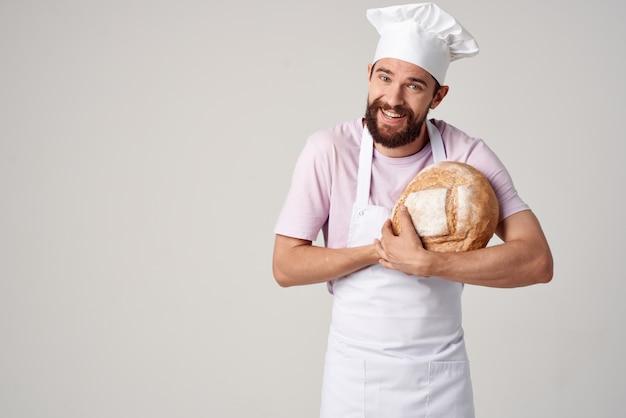 Een man in een koksuniform een bakker met brood in zijn handen aan het koken