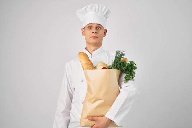 Een man in een koksuniform een pakket met producten restaurantwerk