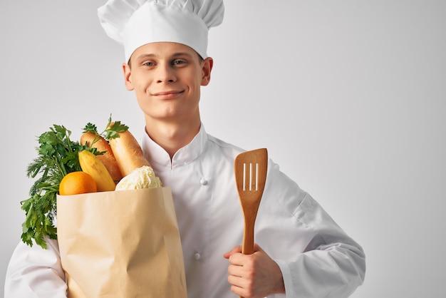 Een man in een koksuniform een pakket producten restaurant werk service