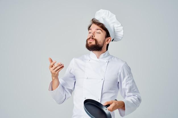 Een man in een koksuniform met een koekenpan in de hand lichte achtergrond