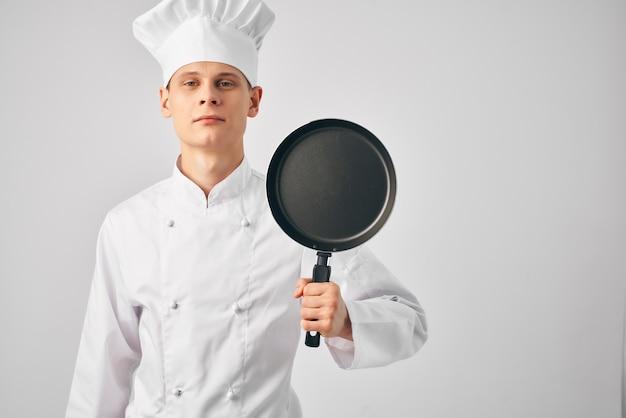 Een man in een koksuniform met een koekenpan in zijn handen kookwerk