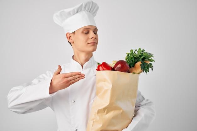 Een man in een koksuniform met een pakket boodschappen bezorging van een restaurantservice