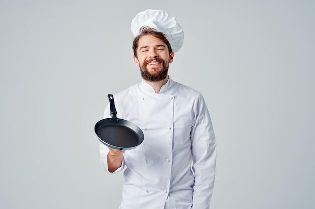 Een man in een koksuniform pan-kokende keukenprofessional