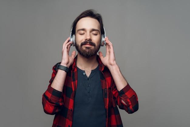 Een man in een koptelefoon luistert aandachtig naar muziek.