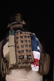 Een man in een militair uniform staat met zijn rug tegen de achtergrond van een oude muur in een vervallen