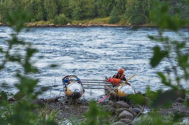 Een man in een opblaasbare catamaran op de rivier