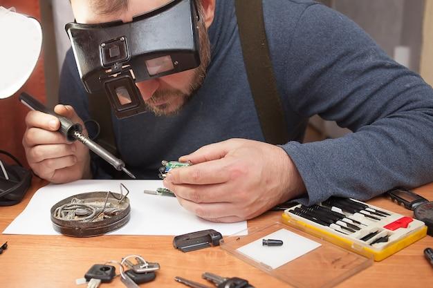 Een man in een optisch apparaat dat elektrische circuits soldeert