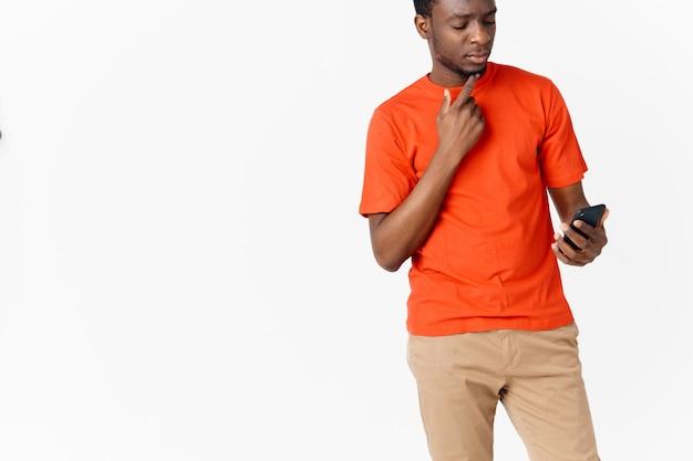 Een man in een oranje t-shirt met een mobiele telefoon op een lichte achtergrond