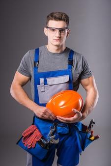 Een man in een outfit staat met een helm in zijn handen.