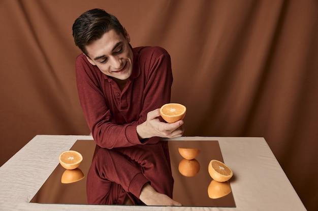 Een man in een overhemd aan een tafel met een spiegelreflectie sinaasappelen stof achtergrond. hoge kwaliteit foto