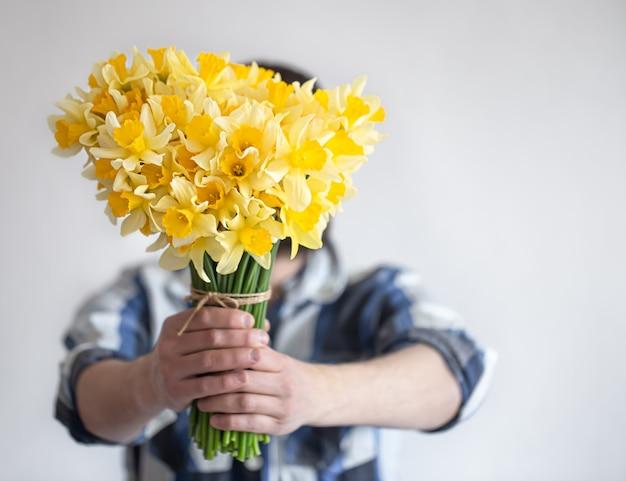 Een man in een overhemd bedekt zijn gezicht met een boeket bloemen