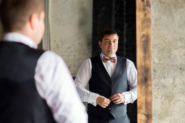 Een man in een overhemd knoopt zijn vest dicht in de weerspiegeling van de spiegel