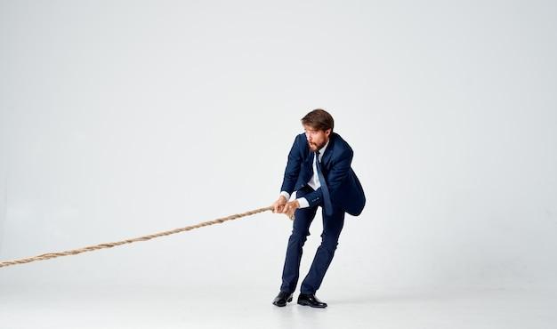Een man in een pak die aan een touw trekt officemanager teamwork