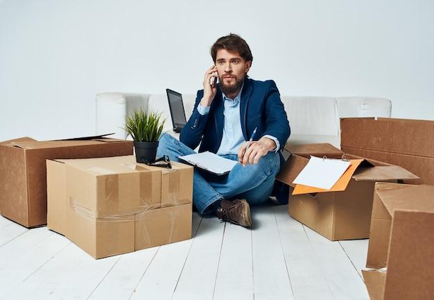 Een man in een pak dozen met dingen die communiceren op het kantoor van de telefoon uitpakken. hoge kwaliteit foto