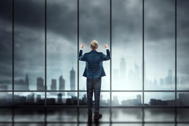 Een man in een pak, een zakenman staat tegen de achtergrond van grote ramen die uitkijken over de stad, kijkt in de verte
