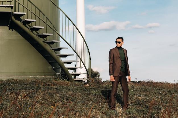 Een man in een pak en een groen golfshirt staat naast een groene windmolen