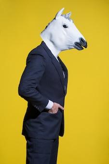 Een man in een pak en een paardenmasker op een gele achtergrond. conceptuele zakelijke achtergrond
