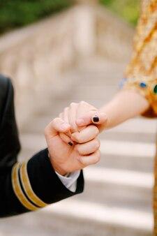 Een man in een pak en een vrouw in een gouden jurk houden elkaars hand teder vast