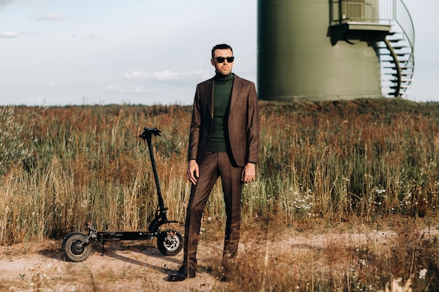 Een man in een pak en groen golfshirt staat naast een elektrische scooter tegen een veld en een blauwe hemel. zakenman dichtbij de scooter. modern concept van de toekomst.