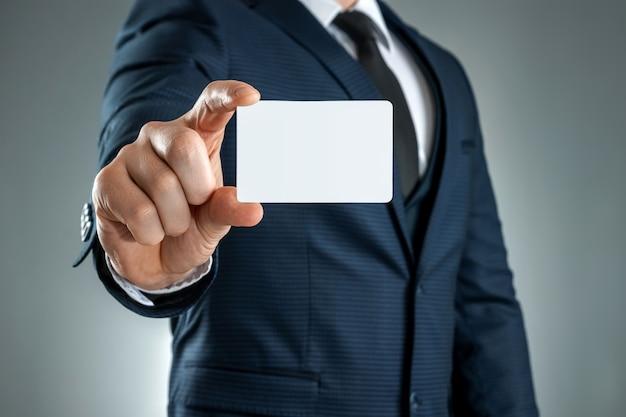 Een man in een pak handen close-up toont een visitekaartje. mockup, lay-out.