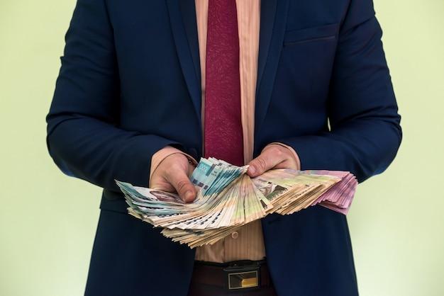 Een man in een pak houdt een grote stapel oekraïens geld vast en toont zijn inkomen. uah. nieuwe bankbiljetten 1000 en 500 hryvnia