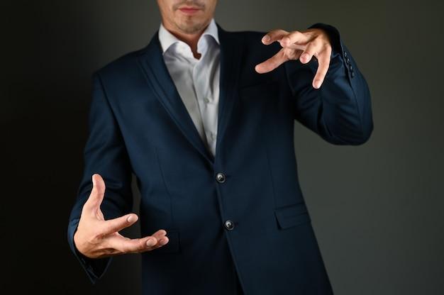 Een man in een pak imiteert het vasthouden van een voorwerp. een man in een pak spreidt zijn handen op een zwarte ruimte. concept: een positieve boodschap in het bedrijfsleven.