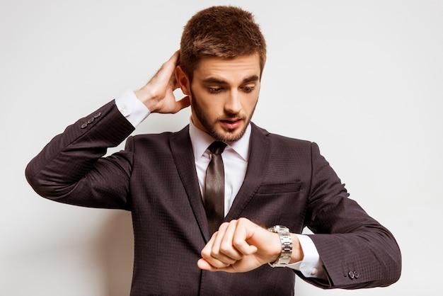 Een man in een pak kijkt op zijn horloge.