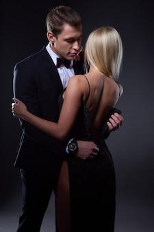 Een man in een pak knoopt zijn jurk open en omhelst zijn vriendin bescheiden