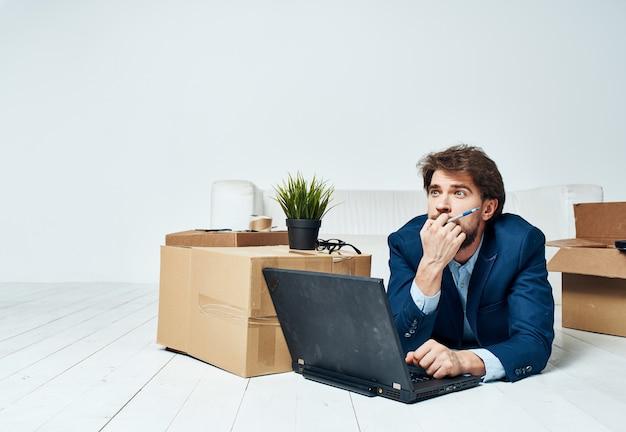 Een man in een pak ligt op de grond met kantoorboxen die een laptoptechnologie uitpakken