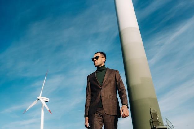 Een man in een pak met een groen golfshirt staat naast een windmolen tegen de achtergrond van het veld en de blauwe lucht. zakenman in de buurt van de windmolens. modern concept van de toekomst.