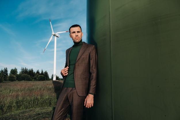 Een man in een pak met een groen golfshirt staat naast een windmolen tegen de achtergrond van het veld en de blauwe lucht
