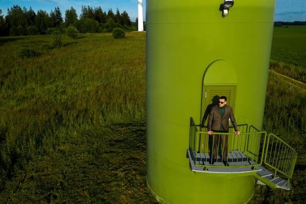 Een man in een pak met een groen golfshirt staat naast een windmolen tegen de van het veld en de blauwe lucht.