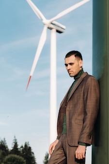 Een man in een pak met een groen golfshirt staat naast een windmolen