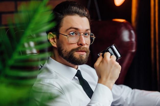 Een man in een pak met een kopje koffie zit op een zwarte leren bank en kijkt naar de camera.