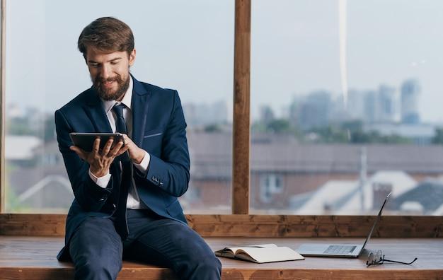 Een man in een pak met een tablet in de handen van een ambtenaar, een professionele zakenman. hoge kwaliteit foto