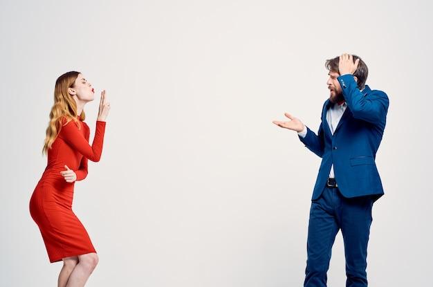Een man in een pak naast een vrouw in een modestudio voor communicatie in een rode jurk