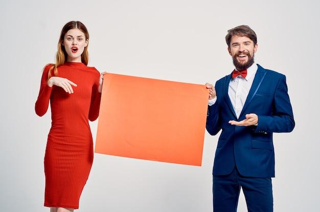 Een man in een pak naast een vrouw in een rode jurk die reclame maakt voor korting op kopieerruimte