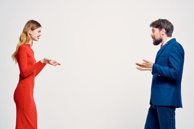 Een man in een pak naast een vrouw in een rode jurk emoties handgebaren geïsoleerde achtergrond. hoge kwaliteit foto