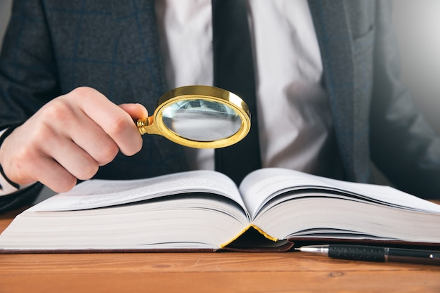 Een man in een pak onderzoekt een boek met een vergrootglas